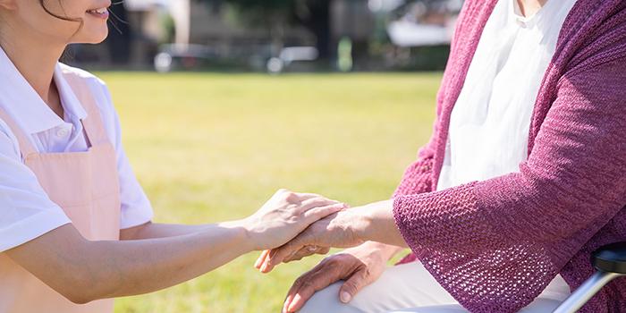お年寄りの手を握る介護士の女性